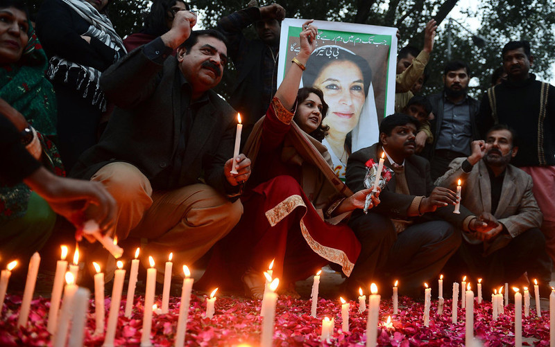 . Activists of ruling Pakistan People\'s Party (PPP) shout slogans as they sit in front of a portrait of the late former Pakistan premier Benazir Bhutto during a candlelight ceremony in Lahore on December 27, 2012, on the fifth anniversary of her assassination. Vast crowds gathered to mark the fifth anniversary of the assassination of former Pakistan premier Benazir Bhutto, and to witness her son launch his own political career.  AFP PHOTO/Arif ALIArif Ali/AFP/Getty Images