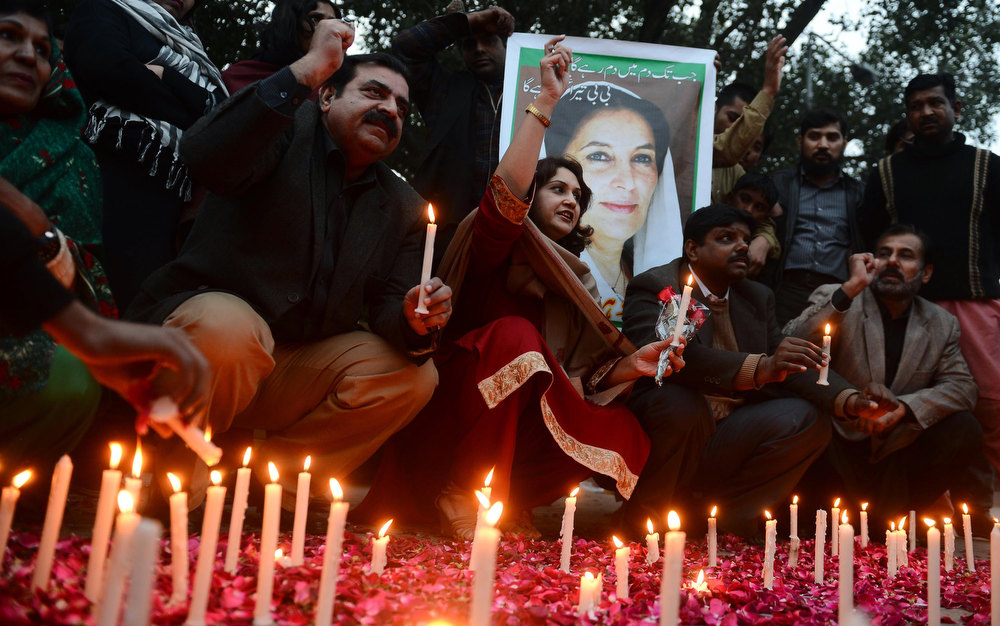 Description of . Activists of ruling Pakistan People's Party (PPP) shout slogans as they sit in front of a portrait of the late former Pakistan premier Benazir Bhutto during a candlelight ceremony in Lahore on December 27, 2012, on the fifth anniversary of her assassination. Vast crowds gathered to mark the fifth anniversary of the assassination of former Pakistan premier Benazir Bhutto, and to witness her son launch his own political career.  AFP PHOTO/Arif ALIArif Ali/AFP/Getty Images