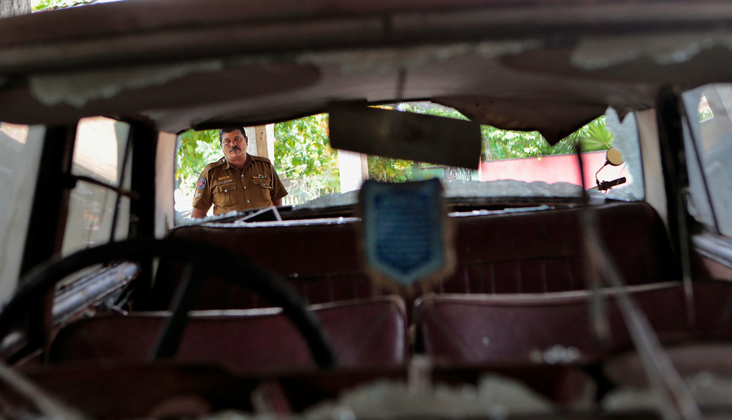 . In this Wednesday, June 25, 2014 photo, a Sri Lankan police officer inspects a car that was vandalized during clashes between Buddhists and Muslims in Darga Town, in Aluthgama about 50 kilometers (31 miles) south of Colombo, Sri Lanka. The onslaught by the Bodu Bala Sena, a hardline Buddhist group that has gained thousands of followers in recent years, killed two Muslims and injured dozens more last month in the worst religious violence Sri Lanka has seen in decades. (AP Photo/Eranga Jayawardena)