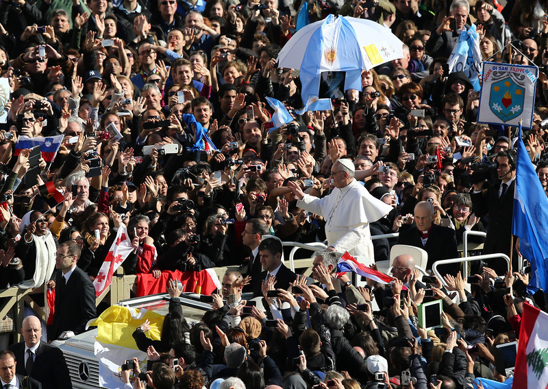 . Pope Francis waves to the crowd as he arrives in the Pope Mobile for his Inauguration Mass in St Peter\'s Square on March 19, 2013 in Vatican City, Vatican. The mass is being held in front of an expected crowd of up to one million pilgrims and faithful who have filled the square and the surrounding streets to see the former Cardinal of Buenos Aires officially take up his role as pontiff. Pope Francis� inauguration takes place in front of Cardinals and spiritual leaders as well as heads of state from around the world.  (Photo by Dan Kitwood/Getty Images)