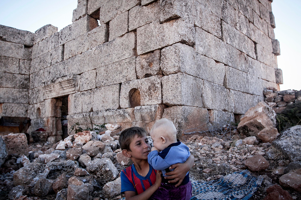 . In this Friday, Sept. 27, 2013 photo, a displaced Syrian child plays with his baby brother near Kafer Rouma, ancient ruins used as temporary shelter by those families who have fled from the heavy fighting and shelling in the Idlib province countryside of Syria. Some 2 million people have fled Syria since the countryís uprising against President Bashar Assad erupted in March 2011, according to the United Nations. Over that time, more than 4 million Syrians also have been internally displaced within the country.(AP Photo)