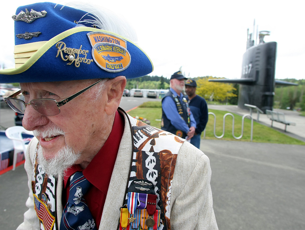 . Ed Ferris of Port Ludlow stand outside Thursday after attending a ceremony at the Naval Undersea Museum Auditorium in Keyport. He was participating in the Tolling the Boats Memorial Day Observance. Ferris served in the U.S. Navy from 1942-67, and was the recipient of the silver star, and four purple hearts. He was on the USS Drum in World war II, and finished serving on a swift boat during the Vietnam conflict. His hat is from severing in Australia during World War II. The event was to honor fallen submarine sailors. (AP Photo/Kitsap Sun, Larry Steagall)