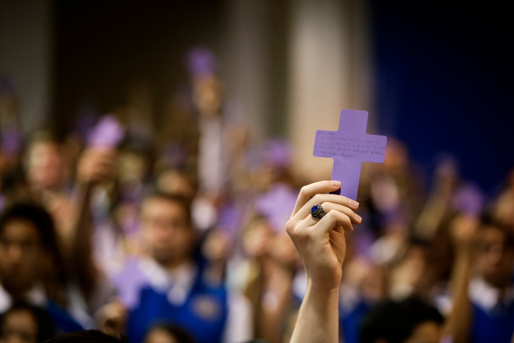 Description of . Students hold up paper crosses during an Ash Wednesday Mass at Santa Margarita Catholic High School on Wednesday, March 5, 2014, in Rancho Santa Margarita, Calif. Ash Wednesday marks the beginning of Lent, a time when Christians commit to acts of penitence and prayer in preparation for Easter Sunday. (AP Photo/Jae C. Hong)