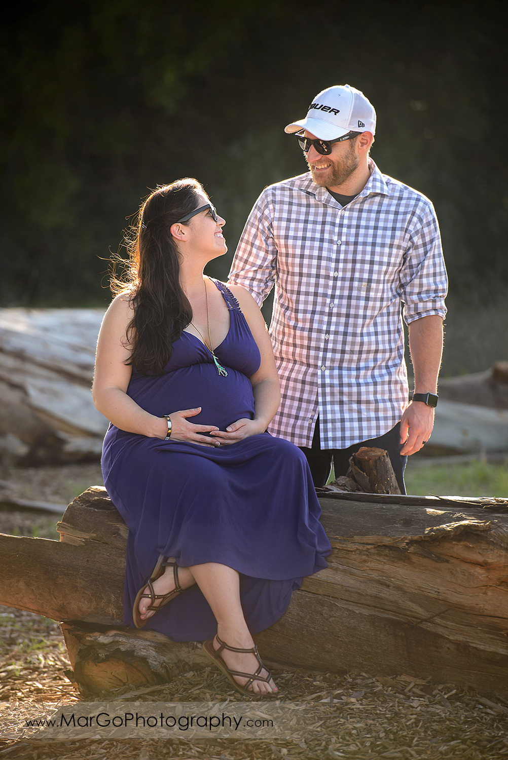man in checkered shirt standing next to pregnant woman in long violet dress sitting on the big log during maternity session at Ulistac Natural Area in Santa Clara