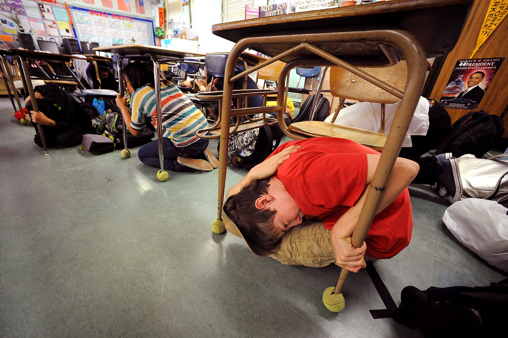 . Students at Millikan Middle School duck under their desks while participating in the Great California Shakeout in Sherman Oaks, CA, October 17, 2013.  (Andy Holzman/Los Angeles Daily News)