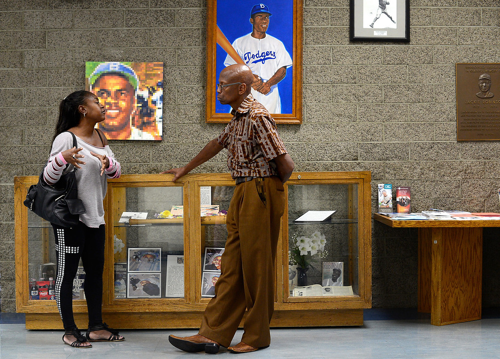 ". ""Extremely disheartening,\"" says Jarvis Emerson, manager of the Jackie Robinson Community Center in Pasadena, of the defacement of the Jackie Robinson statue in New York City. Emerson gives landlord advice to Kimberlisa Best, of Altadena, in the lobby of the Jackie Robinson Community Center Thursday, August 15, 2013. (Photo by Sarah Reingewirtz/Pasadena Star-News)"