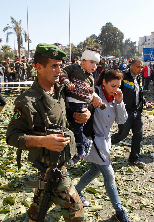 . A Lebanese soldier carries a wounded child from the Islamic Orphanage at the site of explosion near the Kuwaiti Embassy and Iran\'s Chancellery center, in Beir Hassan area at southern suburbs of Beirut, Lebanon, 19 February 2014.  EPA/NABIL MOUNZER