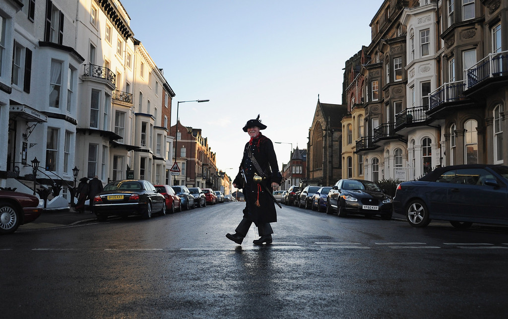 . WHITBY, ENGLAND - NOVEMBER 02:  A man dressed as a pirate crosses the street during the Goth weekend on November 2, 2013 in Whitby, England. The Whitby Gothic Weekend that takes place in the Yorkshire seaside town twice yearly in Spring and Autumn started in 1994 and sees thousands of extravagantly dressed followers of Victoriana, Steampunk, Cybergoth and Romanticism visit to take part in celebrating Gothic culture.  (Photo by Ian Forsyth/Getty Images)