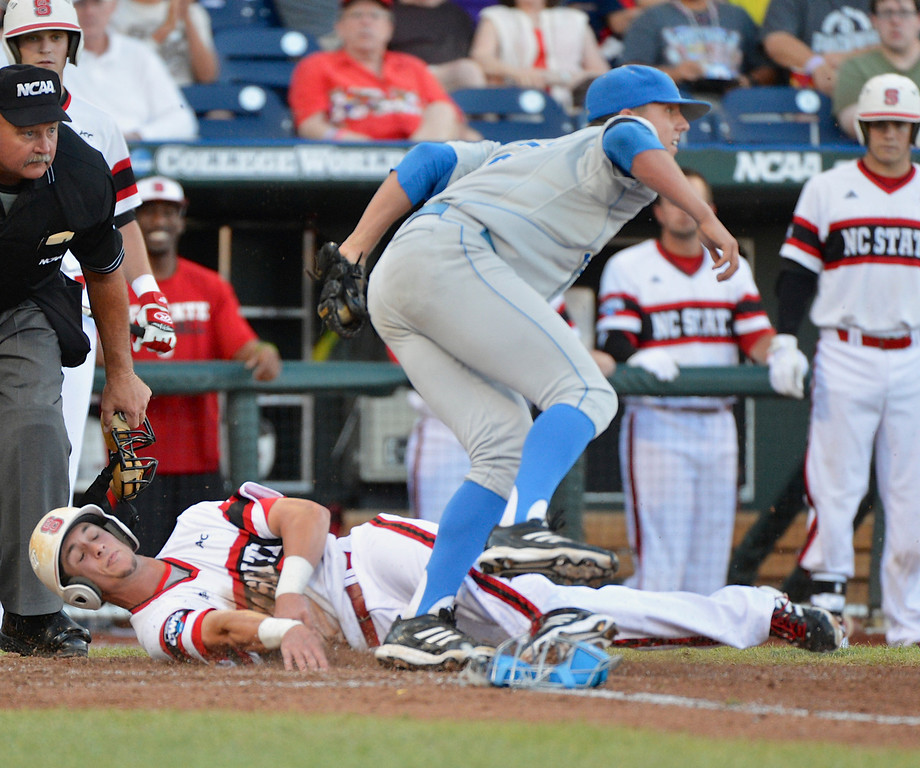 . UCLA pitcher Nick Vander Tuig steps over North Carolina State\'s Jake Armstrong after tagging him out at home plate on a single by Trea Turner in the third inning of an NCAA College World Series game in Omaha, Neb., Tuesday, June 18, 2013. (AP Photo/Ted Kirk)