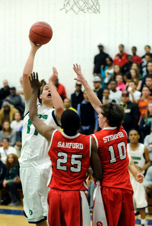 . Blazers forward Andrew Tillman (11) shot over Regis defenders Elijah Sanford and Eric Stemper in the second half. The Overland High School boy\'s basketball team defeated Regis Jesuit 80-66 Tuesday night, December 11, 2012.  Karl Gehring/The Denver Post