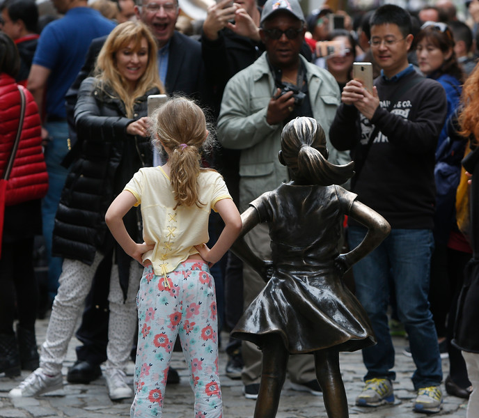 """Tourists take photos of a young girl posing beside the """"Defiant Girl"""" statue in New York City, NY on April 30, 2017. The statue, first intended as a temporary art piece for International Women's Day the previous March, stands directly in front of the infamous Charging Bull statue on Broadway. Arturo Di Modica, the artist for Charging Bull, threatened the city with a lawsuit, stating that Defiant Girl infringes on his copyright. The city has decided to move both statues, citing safety concerns for people along the narrow road island where the statues are currently located."""