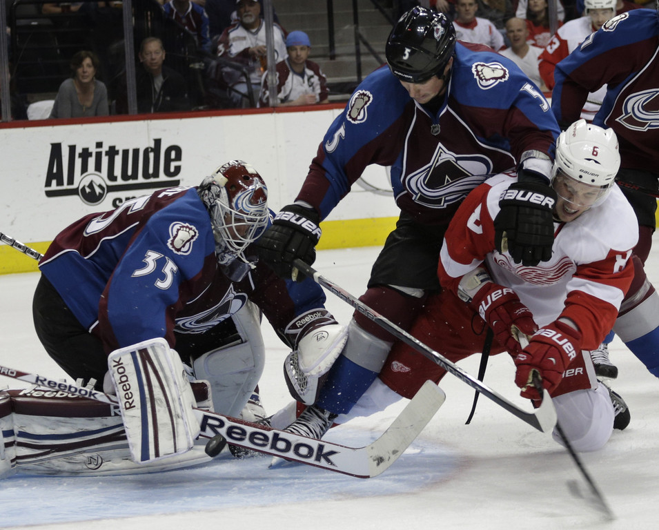 . Colorado Avalanche goalie Jean-Sebastien Giguere (35) lunges for the puck as Avalanche defenseman Shane O\'Brien (5) tries to keep Detroit Red Wings left wing Justin Abdelkader (8) away in the second period of an NHL hockey game on Friday, April 5, 2013, in Denver. (AP Photo/Joe Mahoney)