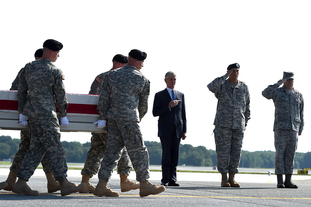 . U.S. Army soldiers carry the flag-draped transfer case containing the remains of U.S. Army Maj. Gen. Harold J. Greene during a dignified transfer, as U.S. Army Secretary John McHugh  (L) holds his hand over his heart, and U.S. Army Chief of Staff Ray Odierno (C), and Dignified Transfer Host, U.S Air Force Col. Richard G. Moore (R) salute, at Dover Air Force Base on August 7, 2014 in Dover, Delaware. A(Photo by Patrick Smith/Getty Images)