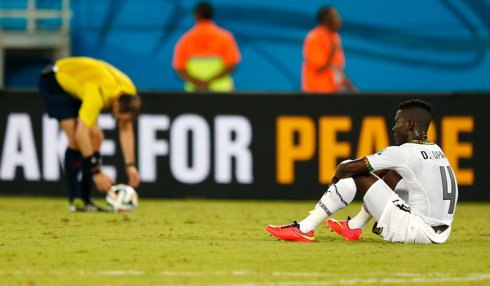 Description of . Ghana's Daniel Opare sits on the pitch after Ghana's 2-1 loss to the United States during the group G World Cup soccer match between Ghana and the United States at the Arena das Dunas in Natal, Brazil, Monday, June 16, 2014. (AP Photo/Julio Cortez)