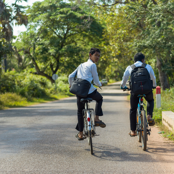 Rear view of two schoolboys riding bicycles, Siem Reap, Cambodia