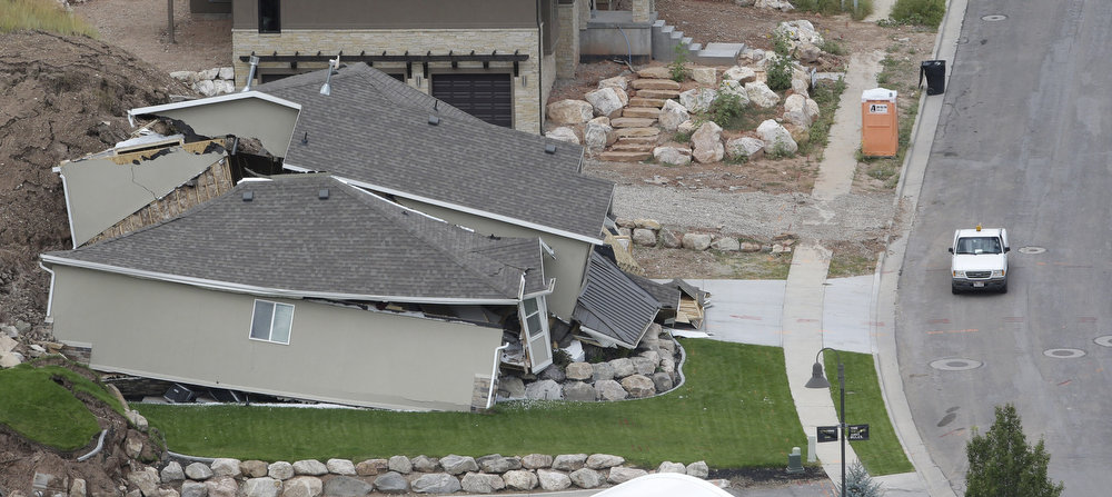 . A home is destroyed following a landslide in a hillside community of North Salt Lake, Utah, Tuesday, Aug. 5, 2014. North Salt Lake officials say more than 20 homes have been evacuated following an early morning landslide that destroyed one hillside home. (AP Photo/Rick Bowmer)