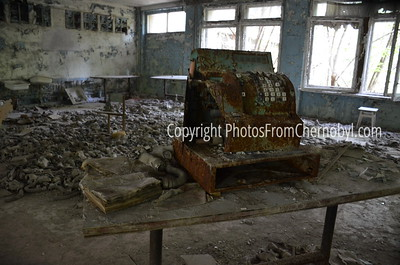 A ruined cash register atop a table, with dozens of gas masks on the floor. Inside a school in Pripyat, Ukraine, that was abandoned after the Chernobyl nuclear disaster.