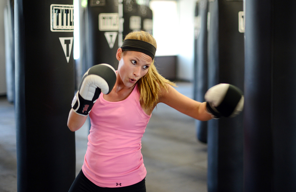 """. Woodbury resident Lindsay Spadino practices her punches at Title Boxing Club in Woodbury on Tuesday, September 10, 2013. She attends a class four to five times weekly and said, \""""It\'s one of the best workouts ever.\""""  (Pioneer Press: Chris Polydoroff)"""