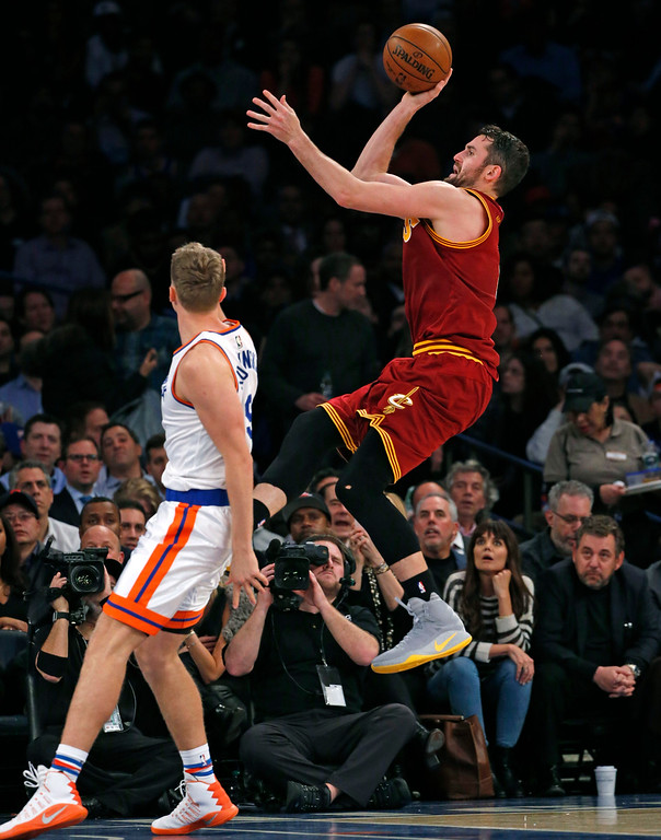 . Cleveland Cavaliers forward Kevin Love (0) attempts a three point shot as New York Knicks forward Mindaugas Kuzminskas (91) watches from the floor in the second half of an NBA basketball game at Madison Square Garden in New York, Wednesday, Dec. 7, 2016. The Cavaliers crushed the Knicks 126-94. (AP Photo/Kathy Willens)
