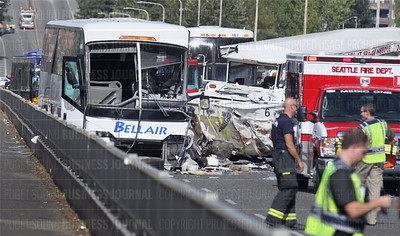 Emergency Services vehicles (right) responding to the scene surround the heavy damage to both the charter bus (left) and a Ride the Duck vehicle (center) in this multiple-fatality crash on the Southbound lanes of the Aurora Bridge in Seattle, Washington
