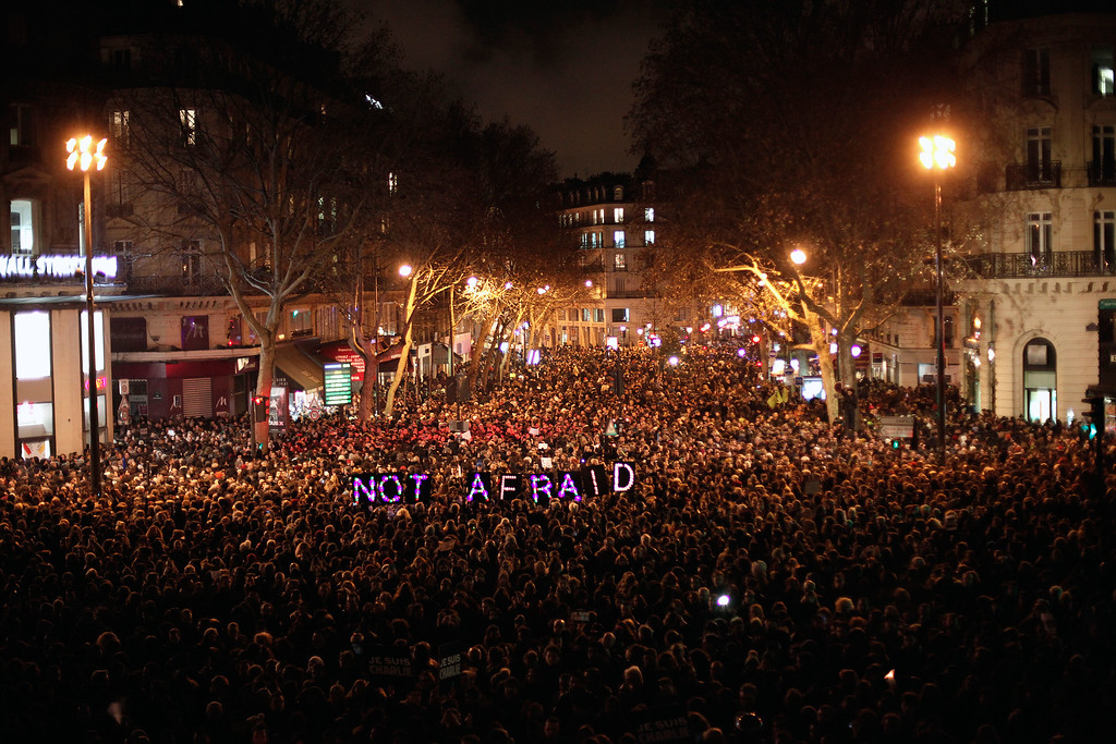 ". People gather to pay respect for the victims of a terror attack against a satirical newspaper, in Paris, Wednesday, Jan. 7, 2015. Masked gunmen shouting ""Allahu akbar!\"" stormed the Paris offices of a satirical newspaper Wednesday, killing 12 people, including the paper\'s editor, before escaping in a getaway car. It was France\'s deadliest terror attack in living memory. (AP Photo/Thibault Camus)"