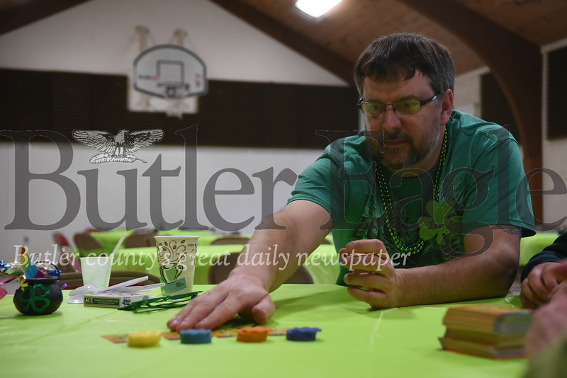 Christ Community United Methodist Church member John Relihan, of West Sunbury, reaches for game cards during St. Patrick Game Night on Sunday.