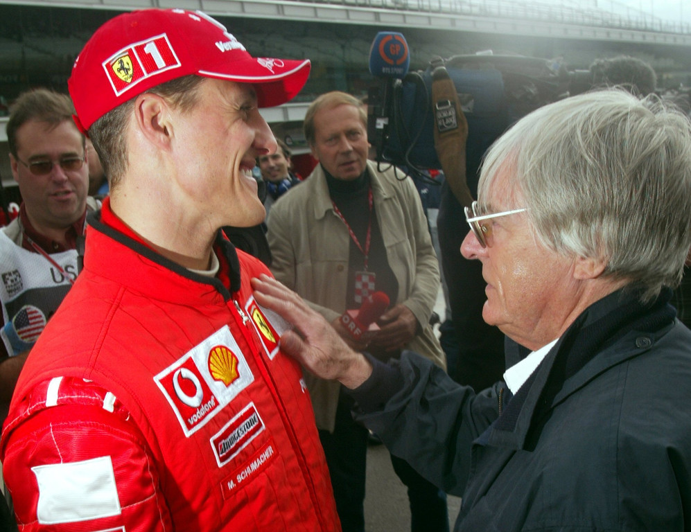 . (dpa) - British head of the formula one racing federation Bernie Ecclestone (R) and German formula one world champion Michael Schumacher talk to each other and smile in front of journalists on the racetrack days before the start of the formula one US Grand Prix in Indianapolis, USA, 26 September 2003. The US Grand Prix is the 15th and the last but one race of this year\'s formula one season. Photo by: Gero Breloer/picture-alliance/dpa/AP Images