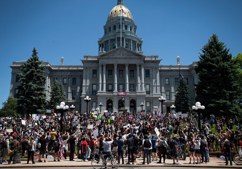 People chant on the steps of the Colorado Capitol during a protest in response to the police killing of George Floyd, an unarmed black man in Minneapolis, in Denver, Colo. on Friday, May 29, 2020.