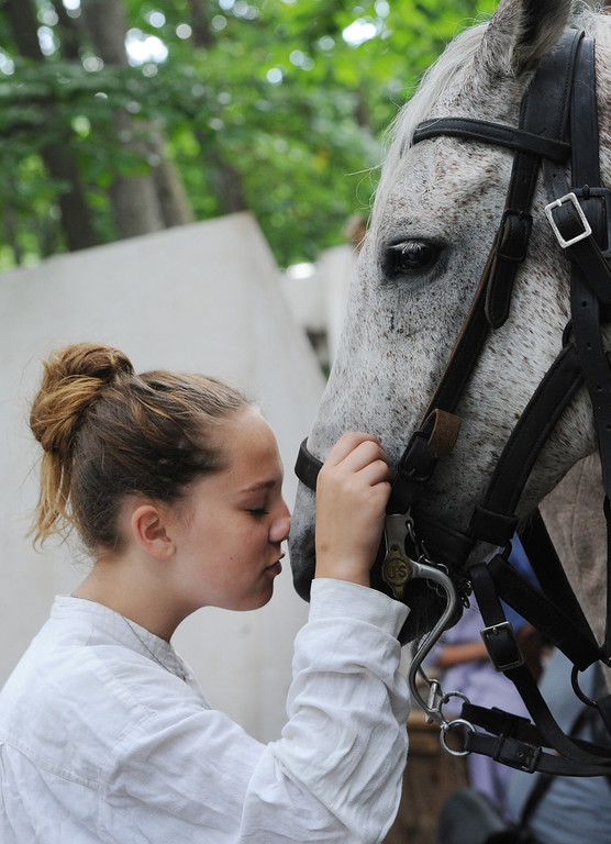 . Megan Savona goes nose to nose with Cricket, a horse belonging to Chris Slocum,  a reenactor with the Southwest cavalry brigade, as the duo stands among the Confederate army\'s encampment in Gettysburg, Pa., for the 150th celebration of the Battle of Gettysburg on Thursday, June 27, 2013. (AP Photo/York Daily Record, Jason Plotkin)