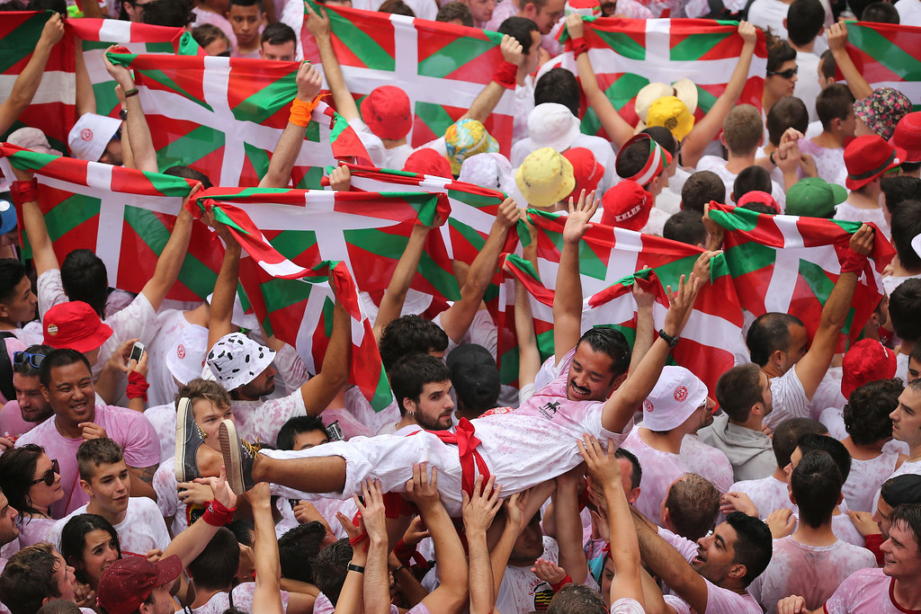 . Revellers cheer and throw red wine as they prepare for the opening and the firing of the  \'Chupinazo\' rocket which starts the 2014 Festival of the San Fermin Running of the Bulls on July 6, 2014 in Pamplona, Spain. The annual Fiesta de San Fermin, made famous by the 1926 novel of US writer Ernest Hemmingway entitled \'The Sun Also Rises\', involves the daily running of the bulls through the historic heart of Pamplona to the bull ring.  (Photo by Christopher Furlong/Getty Images)