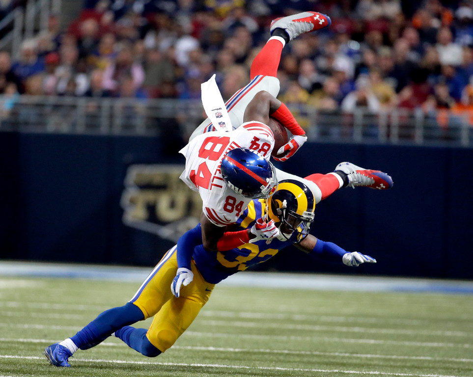 . New York Giants tight end Larry Donnell, top, is upended by St. Louis Rams cornerback E.J. Gaines after catching a pass for a 4-yard gain during the first half of an NFL football game Sunday, Dec. 21, 2014, in St. Louis. (AP Photo/Charlie Riedel)