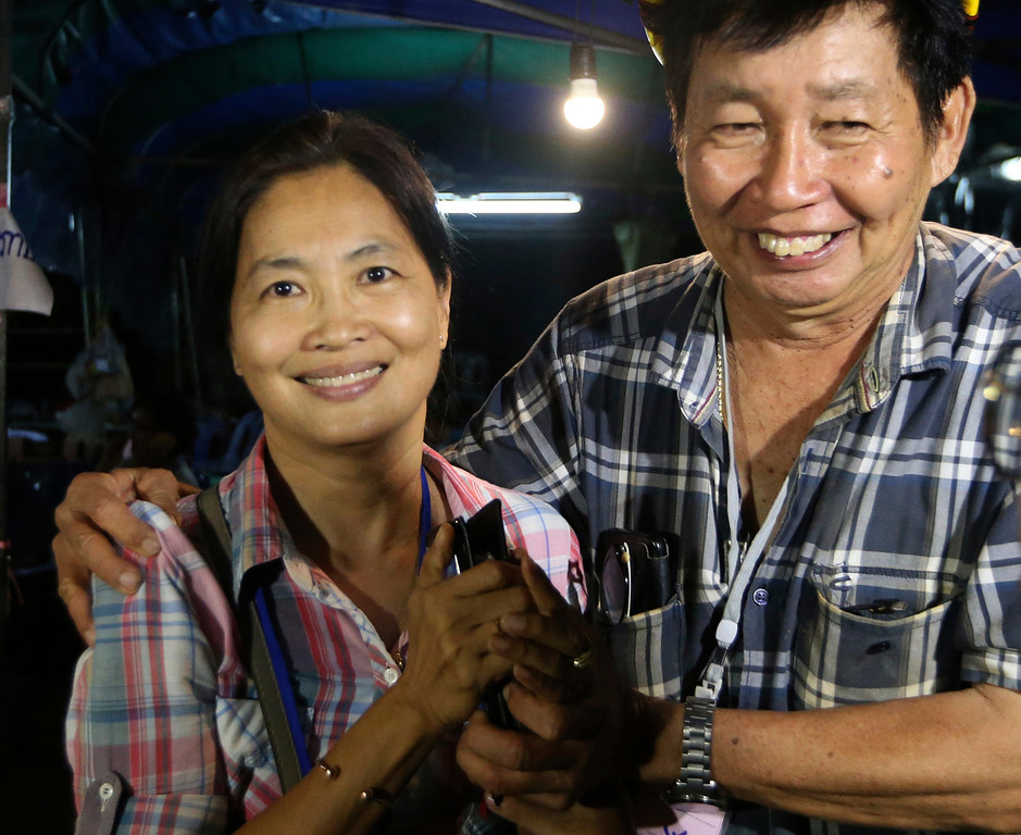 . Family members smile after hearing the news that the missing 12 boys and their soccer coach have been found, in Mae Sai, Chiang Rai province, in northern Thailand, Monday, July 2, 2018. A Thai provincial governor says all 12 boys and their coach have been found alive in the cave where they went missing over a week ago in northern Thailand. (AP Photo/Sakchai Lalit)