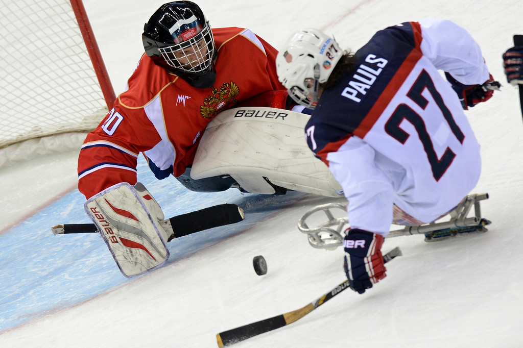 . United States\' Joshua Pauls (R) vies with Russia\'s goalie Vladimir Kamantcev  during Sledge Hockey Final match between Russia and USA at XI Paralympic Olympic games in the Shayba stadium close near Sochi on March 15, 2014. AFP PHOTO/KIRILL  KUDRYAVTSEV/AFP/Getty Images
