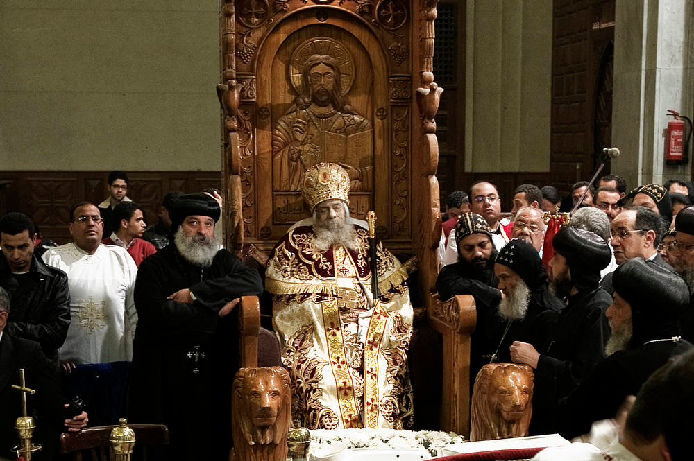 Description of . Egyptian Coptic priests gather around the body of Pope Shenuda III, the spiritual leader of the Middle East's largest Christian minority, sitting dressed in formal robes on a wooden throne at the Saint Mark's Coptic Cathedral in Cairo's al-Abbassiya district on March 19, 2012. Pope Shenuda died at the age of 88, after a long battle with illness and based on his wishes he will be buried on March 20, at St. Bishoy monastery in Wadi Natrun in the Nile Delta where he spent his time in exile after a dispute with late president Anwar Sadat.AFP PHOTO/GIANLUIGI  GUERCIA/AFP/Getty Images