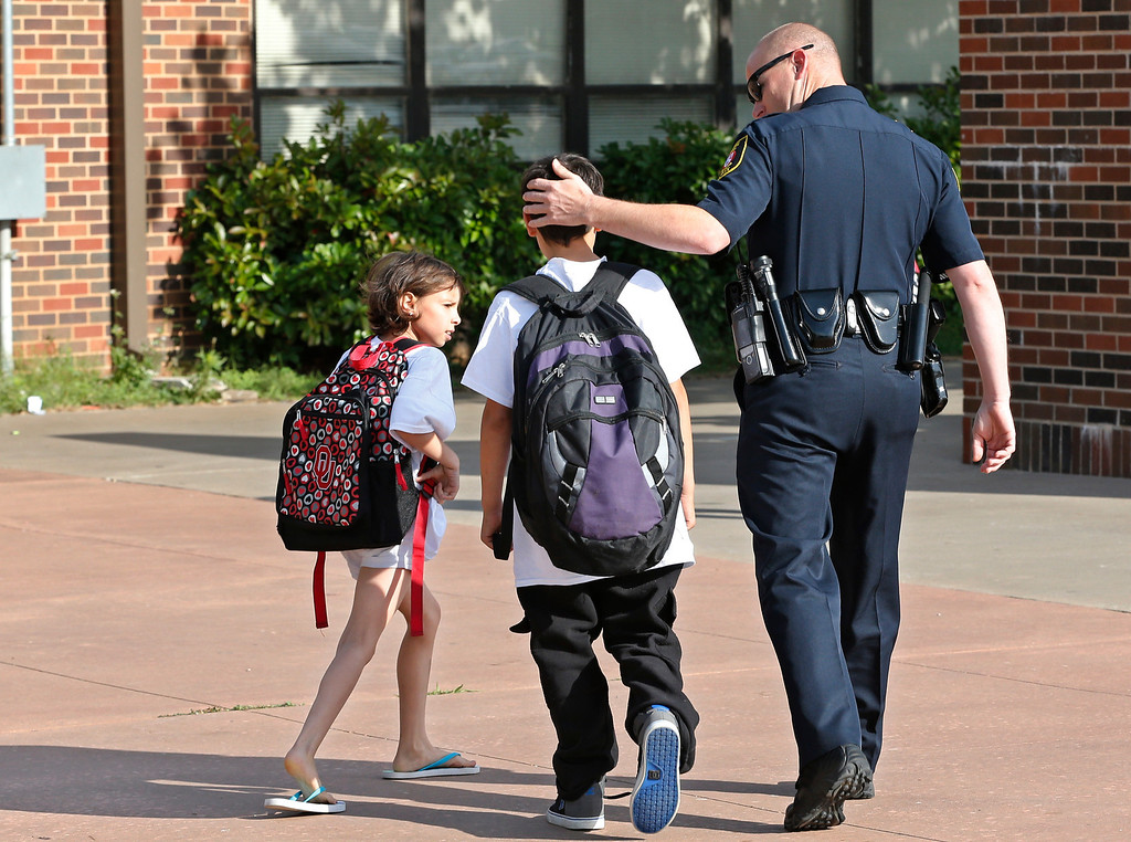 . Xavier Delgado, center, and his sister, Haley Delgado, left, are greeted by Moore police Sgt. Alan Wallace, right, as arrive for the start of school at the temporary site for Plaza Towers Elementary school in Moore, Okla., Tuesday, May 20, 2014, one year after the May 20, 2013 tornado destroyed Plaza Towers school, leaving Xavier Delgado and other third graders trapped in the rubble. Wallace was on site at the school helping to rescue children the day of the tornado. (AP Photo/Sue Ogrocki)