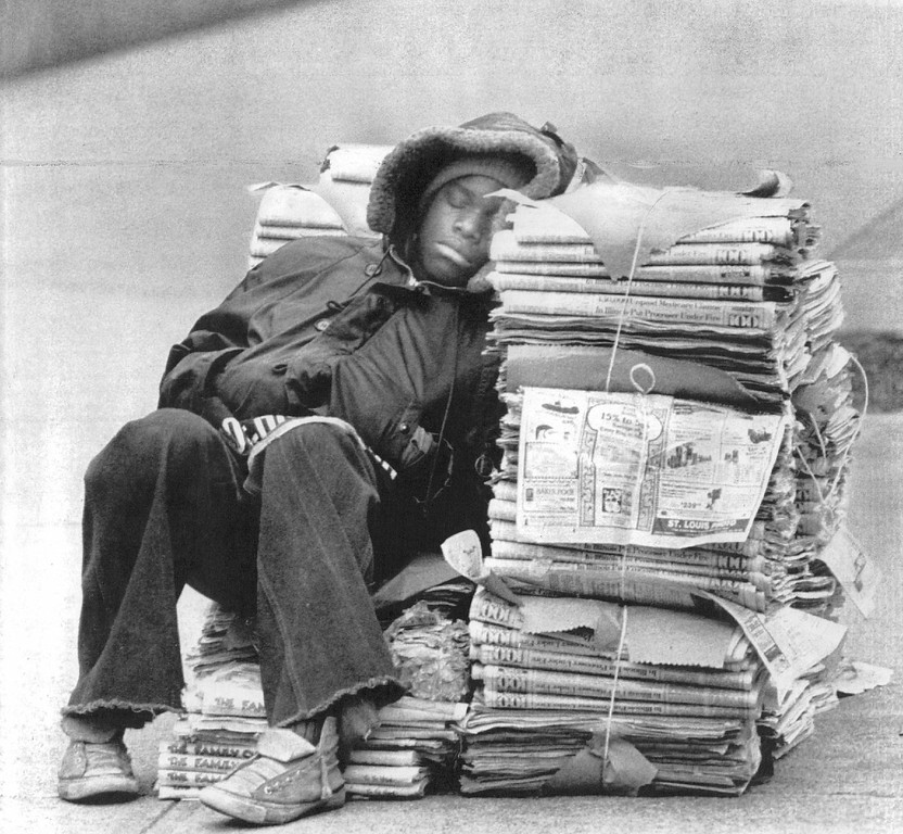 . Orlando Mondaine, trying to beat the early-morning chill, snuggles up to a stack of newspapers for a short nap in St. Louis Sunday. Business wasn\'t really slow. Mondaine  was just waiting for churchgoers to leave services at the St. Louis Cathedral before selling his papers. 1979. (UPI Telephoto)
