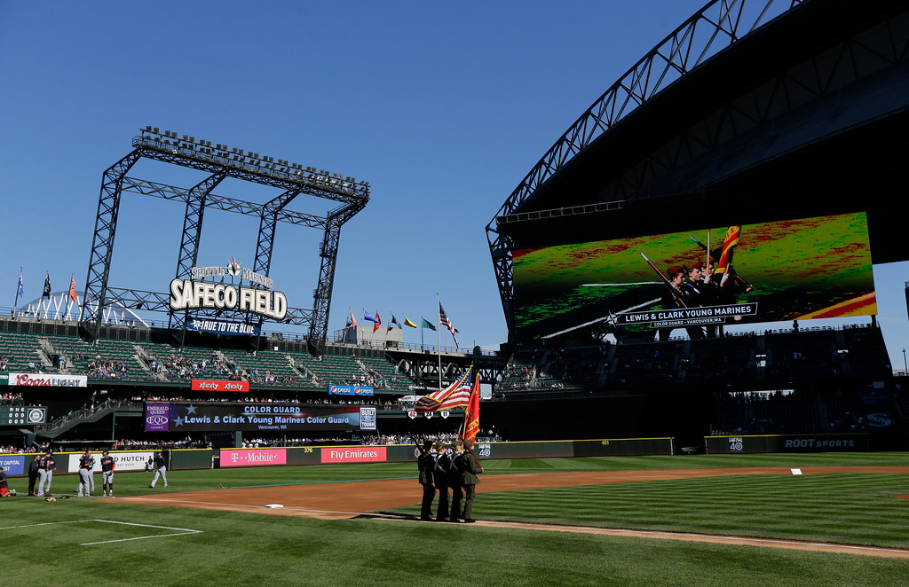 . A color guard walks with the flag at Safeco Field before singing of the national anthem prior to a baseball game between the Seattle Mariners and the Cleveland Indians, Sunday, Sept. 24, 2017, in Seattle. (AP Photo/Ted S. Warren)