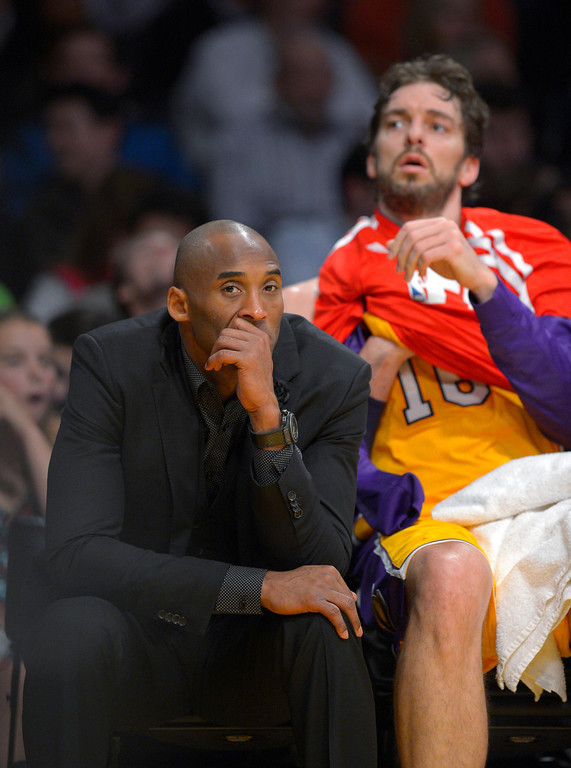 . Los Angeles Lakers guard Kobe Bryant, left, watches from the bench along with center Pau Gasol, of Spain, during the first half of an NBA basketball game against the Utah Jazz, Friday, Jan. 3, 2014, in Los Angeles. (AP Photo/Mark J. Terrill)