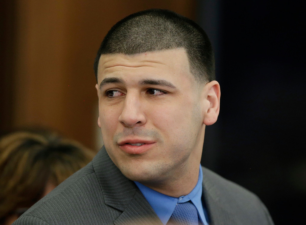 . Former New England Patriots tight end Aaron Hernandez turns to look toward his fiancee Shayanna Jenkins Hernandez as he reacts to his double murder acquittal at Suffolk Superior Court Friday, April 14, 2017, in Boston. Hernandez stood trial for the July 2012 killings of Daniel de Abreu and Safiro Furtado who he encountered in a Boston nightclub. The former NFL player is already serving a life sentence in the 2013 killing of semi-professional football player Odin Lloyd. (AP Photo/Stephan Savoia, Pool)