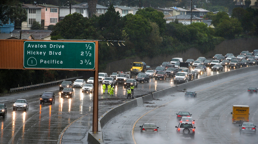 . Caltrans workers clear debris from the fllooded southbound lanes of Interstate 280 at Sneath Lane in San Bruno, Calif., on Thursday, Dec. 11, 2014. Traffic was backed up to Daly City for hours.(John Green/ Bay Area News Group)