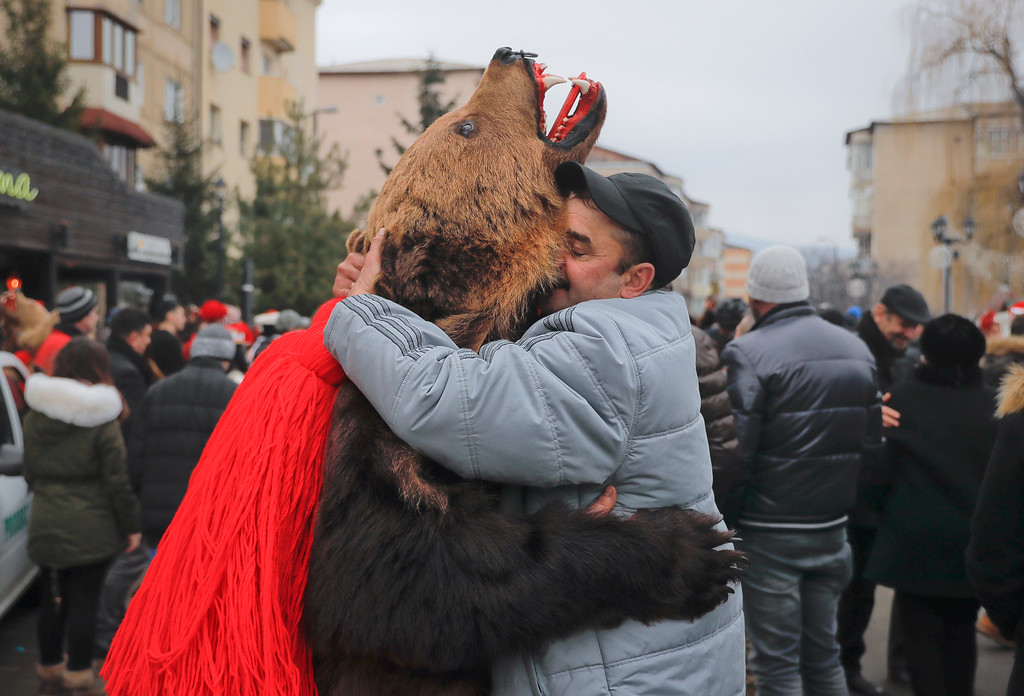 . In this Saturday, Dec. 30, 2017, picture men, one wearing a bear fur costume, hug during an annual bear parade in Comanesti, Romania. Hundreds of people descend on the sleepy northern Romanian city of Comanesti every year dressed head to toe like bears, in costumes made from real fur, with the heads attached. It\'s a tradition that originated in pre-Christian times, when dancers wearing colored costumes or animal furs went from house to house in villages, singing and dancing to ward off evil. (AP Photo/Vadim Ghirda)