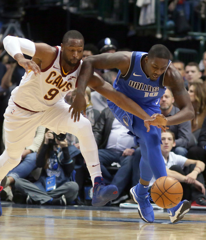 . Dallas Mavericks forward Dorian Finney-Smith (10) and Cleveland Cavaliers guard Dwyane Wade (9) chase the ball during the first half of an NBA basketball game in Dallas, Saturday, Nov. 11, 2017. (AP Photo/LM Otero)