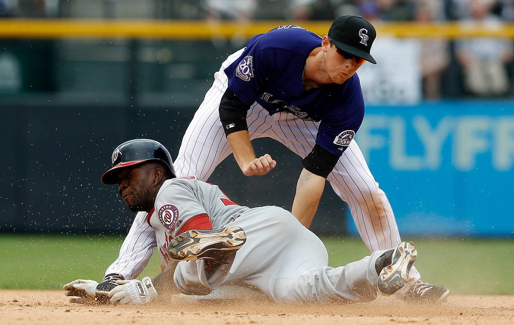 . Washington Nationals pinch hitter Roger Bernadina, bottom, slides safely into second base with a double as Colorado Rockies second baseman DJ LeMahieu applies a late tag in the eighth inning of the Nationals\' 5-4 victory in a baseball game in Denver, Thursday, June 13, 2013. (AP Photo/David Zalubowski)