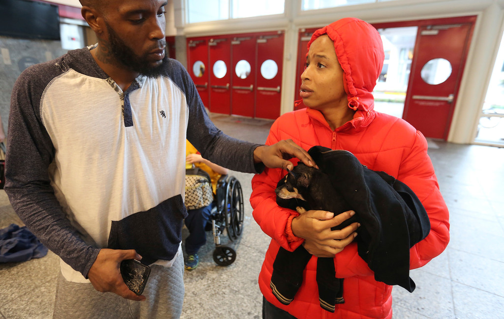 . Brandon Spears, left, checks on his wife D\'Ona Spears and her dog Missy at a shelter for flood evacuees in the convention center in downtown Houston, Texas, Sunday, Aug. 27, 2017. Spears and her family walked to the shelter after her home was flooded with water from the Buffalo Bayou. (AP Photo/LM Otero)