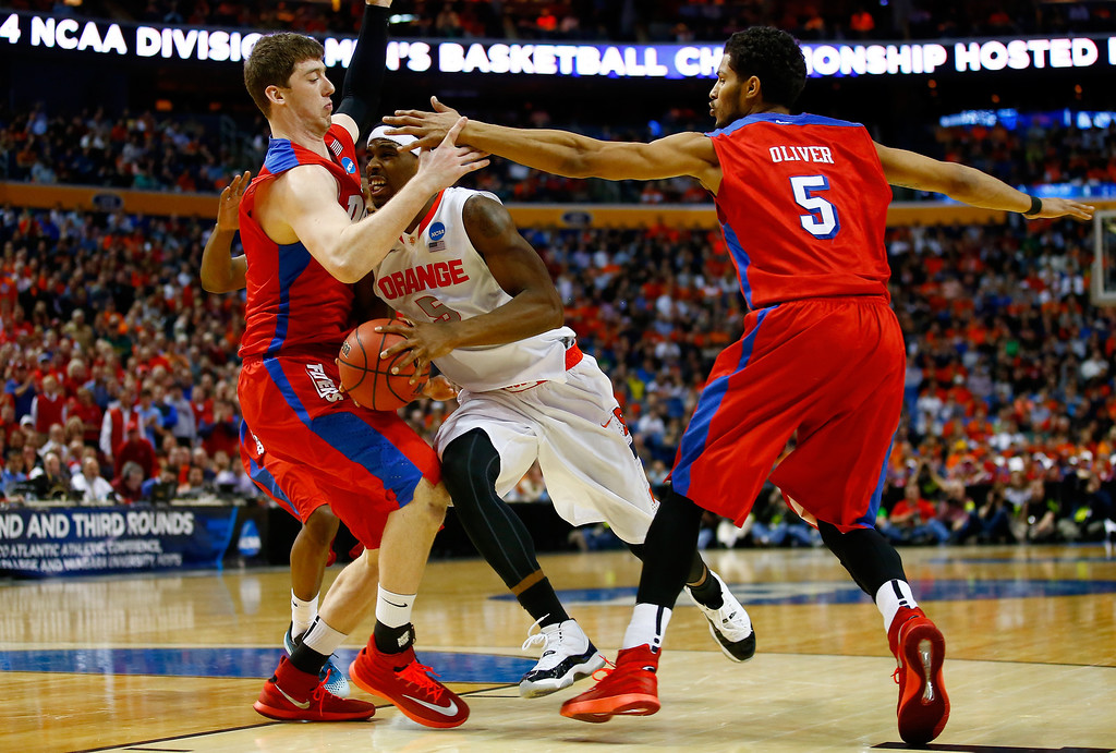 . BUFFALO, NY - MARCH 22: C.J. Fair #5 of the Syracuse Orange goes to the basket as Matt Kavanaugh #35 and Devin Oliver #5 of the Dayton Flyers defend during the third round of the 2014 NCAA Men\'s Basketball Tournament at the First Niagara Center on March 22, 2014 in Buffalo, New York.  (Photo by Jared Wickerham/Getty Images)
