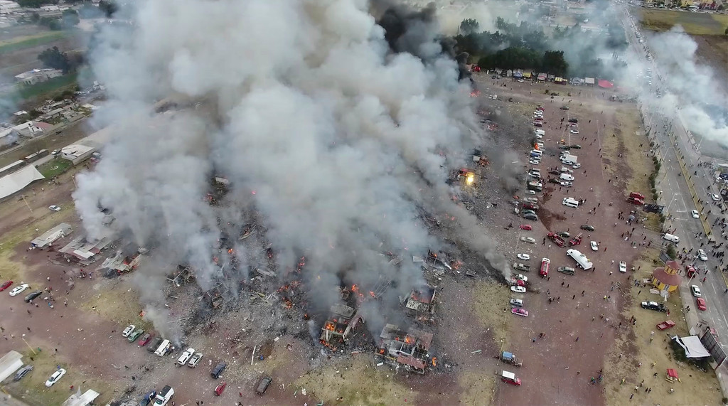 . This image made from video provided by APTN, shows a view from a drone of smoke billowing from the San Pablito Market, where an explosion ripped through a fireworks market in Tultepec, Mexico, Tuesday, Dec. 20, 2016. Sirens wailed and a heavy scent of gunpowder lingered in the air after the afternoon blast at the market, where most of the fireworks stalls were completely leveled. According to the Mexico state prosecutor there are dozens dead. (Pro Tultepec via APTN)