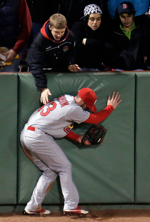 . St. Louis Cardinals\' Shane Robinson runs into the wall after catching a ball hit by Boston Red Sox\'s Dustin Pedroia during the fifth inning of Game 1 of baseball\'s World Series Wednesday, Oct. 23, 2013, in Boston. (AP Photo/Charlie Riedel)
