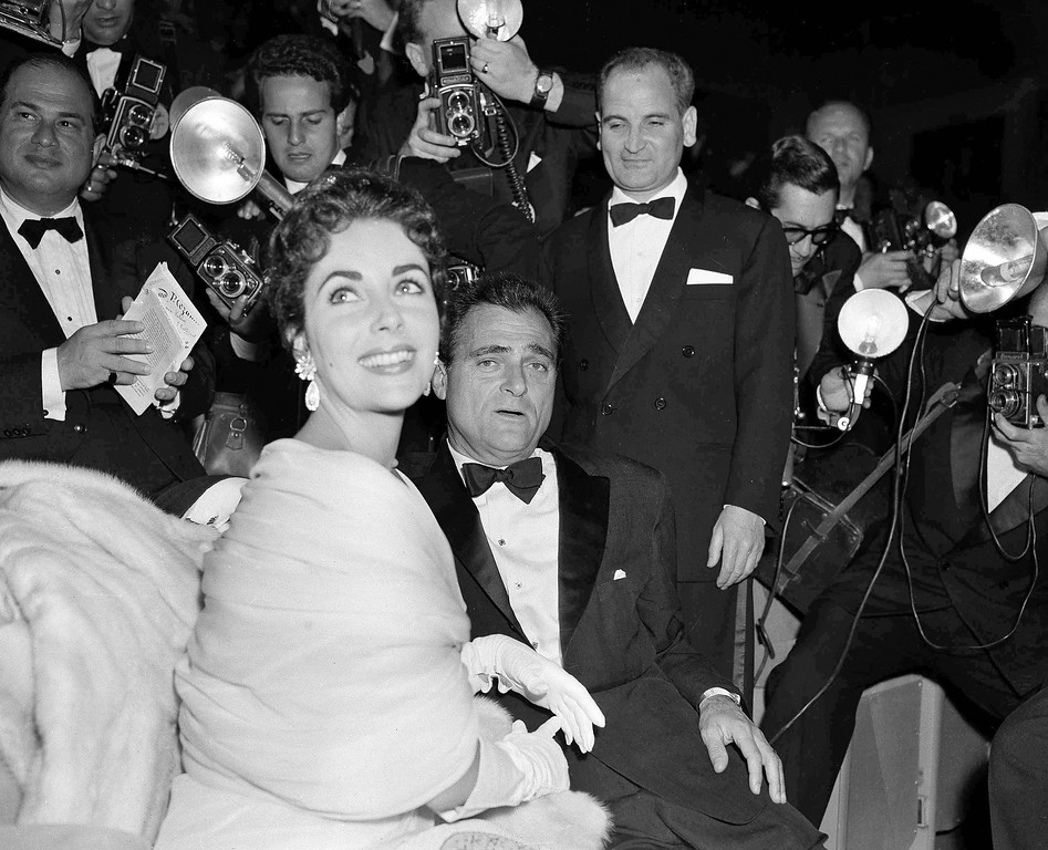 . U.S. film star Elizabeth Taylor and her husband, producer Mike Todd are surrounded by photographers at the Cannes Film Festival at Cannes, France, May 2, 1955.  (AP Photo/Babout)