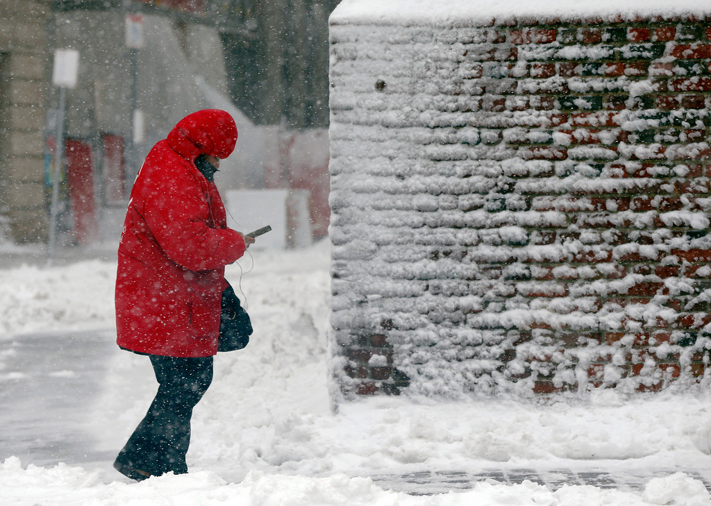 . A pedestrian walks past a snow-coated wall during a snowstorm, Tuesday, March 13, 2018, in Boston. (AP Photo/Michael Dwyer)