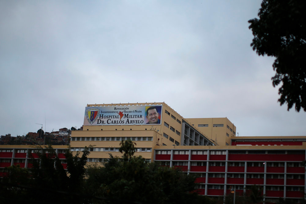 Description of . A banner with a portrait of Venezuela's President Hugo Chavez is seen on the military hospital after his surprise return to Caracas February 18, 2013. Chavez made a surprise return from Cuba on Monday more than two months after surgery for cancer that has jeopardized his 14-year rule of the South American OPEC member. The 58-year-old socialist leader underwent a six-hour operation in Cuba on December 11. He had not been seen or heard in public since then until photos were published of him on Friday. Banner reads,